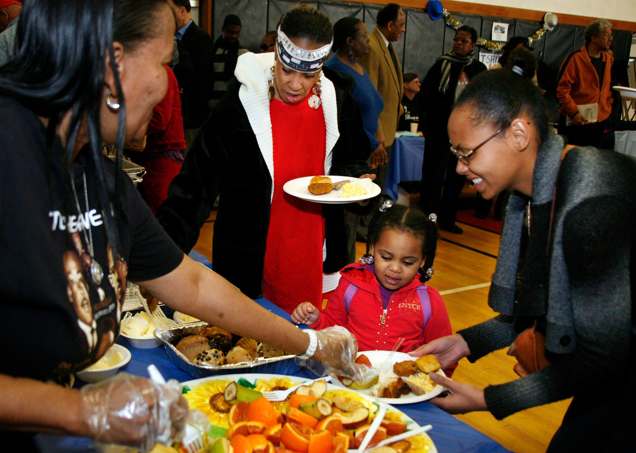 Kailah Theard, right, helps her daughter Ameerah Mohamed get breakfast at the Community Center in Marin City as part of the Martin Luther King Day festivities in Marin City, Calif. on Monday, January 16, 2012.  (Special to the IJ/James Cacciatore Photo)
