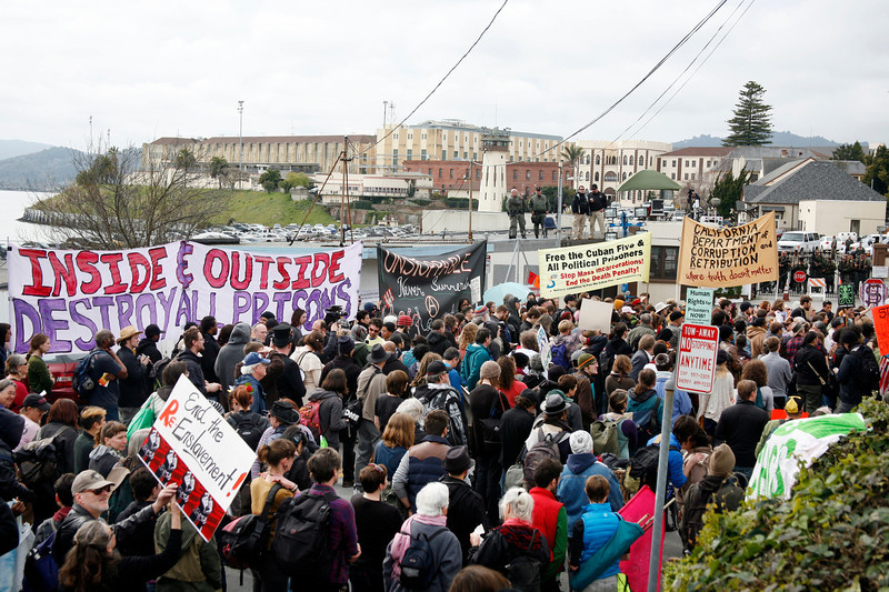 A crowd of Occupy protesters listen to speeches under the watchful eyes of police at the main gate to San Quentin Prison in San Quentin, Calif. on Monday, February 20, 2012.  (Special to the IJ/James Cacciatore)