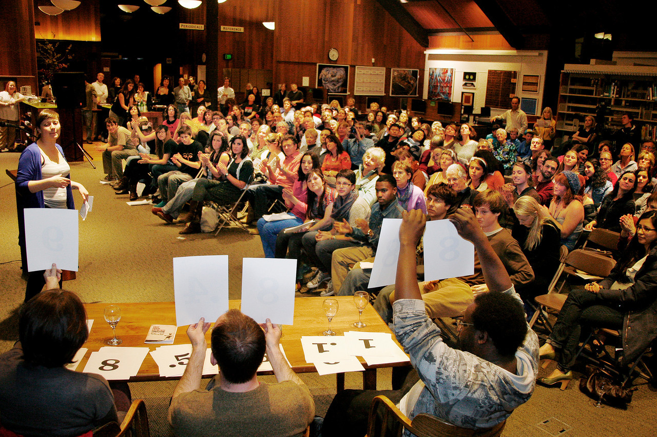 The judges hold up score sheets after a poet's reading at the First Friday Slam Poetry Competition at the Mill Valley Library in Mill Valley, Calif. on Friday, March 2, 2012. (Special to the IJ/James Cacciatore)