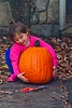 Mia picking up a pumpkin - 2016-10-29