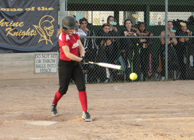 Taylor Poelker puts the ball in play for Marine City Cardinal Mooney while teammate Shanna Kowalewski takes a practice swing. Mooney lost both games of a doubleheader Tuesday afternoon in Royal Oak.