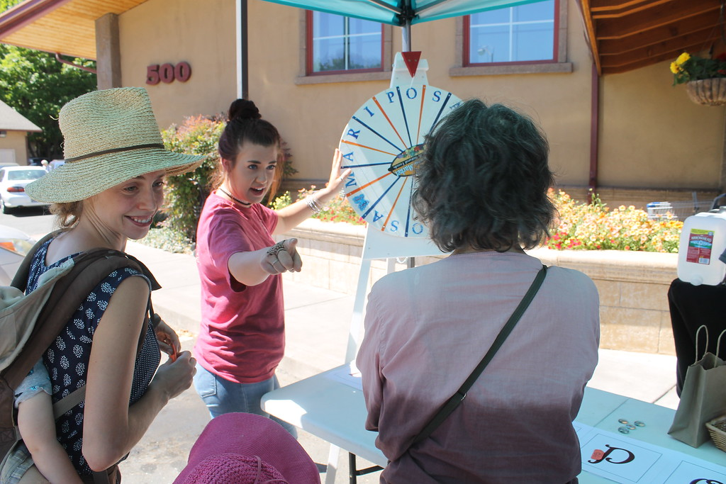 . ARIEL CARMONA JR/THE WILLITS NEWS Tauna Hincker spins the wheel for customers Saturday. Those who made a purchase had the opportunity to win food and prizes.