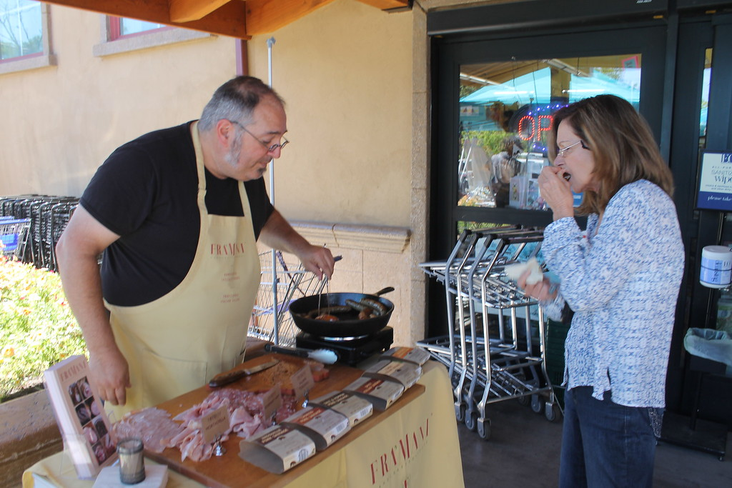 . ARIEL CARMONA JR/THE WILLITS NEWS James Mousigian, regional sales manager at Fra\'Mani Handcrafted Foods offers a customer a sample of his breakfast sausages at Mariposa Market Saturday