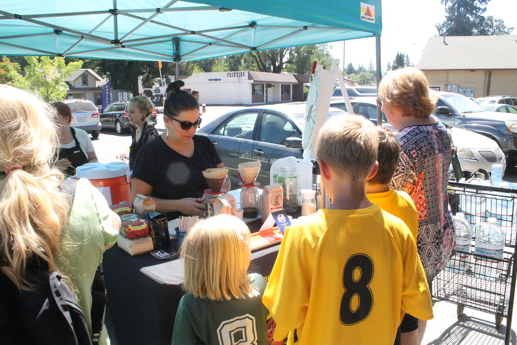 . ARIEL CARMONA JR/THE WILLITS NEWS Luci Ramirez, co-owner of Humboldt Bay Coffee organic company offers samples to customers Saturday.