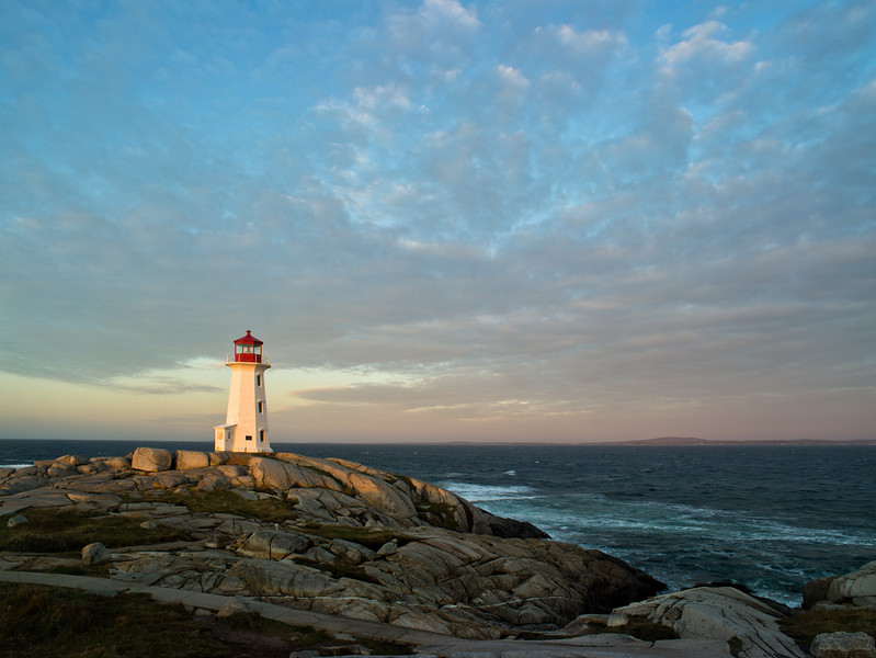 sun breaking through the clouds with Peggy's Cove Lighthouse
