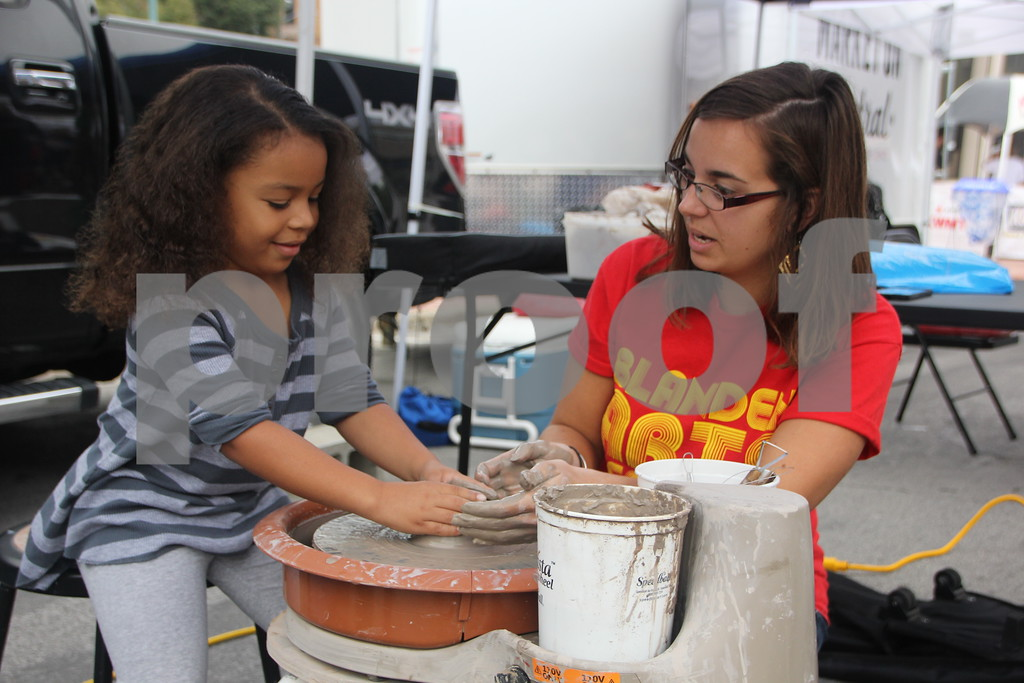 On Saturday, August 27, 2016, Central Avenue in Fort Dodge was a buzz again with Market on Central, which offers plenty of vendors and things to see and do for everyone. Pictured (left to right) is : Melora Osai and Hope Opthier, as she Melora and observers how to throw a pot on the potter's wheel.