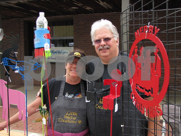 Mary and Gary Little of 'Little Metal Creations' stand among some of their metal art they had at Market on Central.