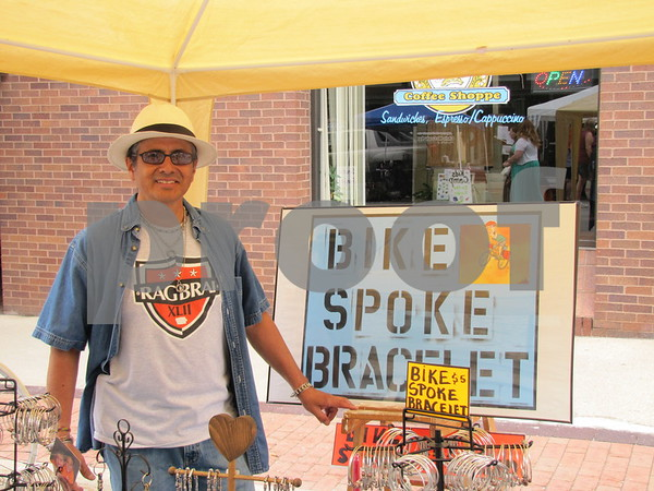 Antonio Ron in his booth featuring handmade jewelry from bicycle spokes.