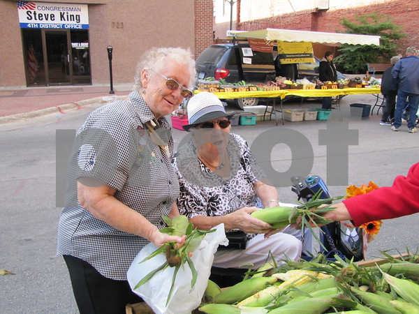Anita Jo Cowen from California, and Ruth Eudy of Eagle Grove looking over the sweet corn from Black's Heritage Farm.