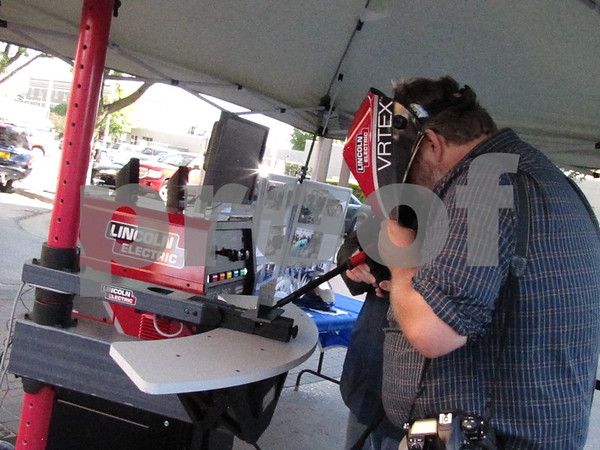 Hans Madsen tries his hand at the welding simulator in the ICCC booth at Market on Central.