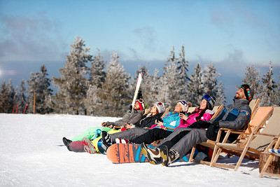 friends skiers relax in chairs on the mountain top