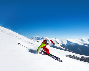 A man is skiing down the hill on the steep slope in Carpathians. Ukraine. High mountain area.
