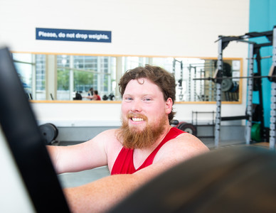 Student Tyler Cobb poses for a photo while working on the bench press at the Dugan Wellness Center.