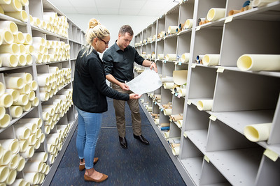 Library Specialist II Shelby Gonzalez (left), and SQL Coordinator Bryan Gillis examine archived maps in the Mary and Jeff Bell Library collections.