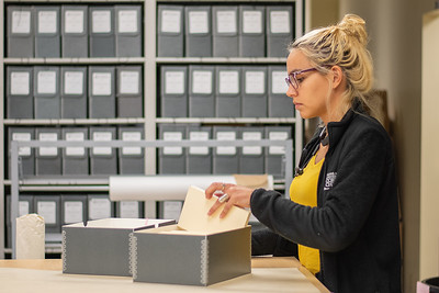Libary Specialist Shelby Gonzalez looks through  journals archived in the Mary and Jeff Bell Library collection.