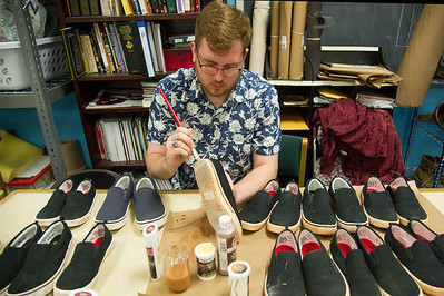 """Dakota Finney painting the shoes for a production of William Shakespeare's """"Julius Caesar,""""."""