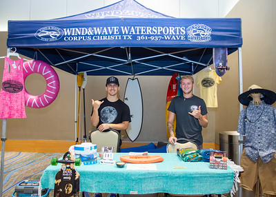 Andre Saenz (left) and Brandon Lewis from Wind & Wave Watersports wait for students to come to their booth during the Corpus Christi Community Fair.