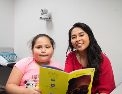 """Karligth Flurs (right) reads Red Rocket Readers """"Volcanoes"""" to Marijo Acosta"""