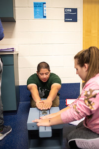 Morgan Raskieioz (right) assists student Christian Melo on the sit and reach for Kinesiology fitness test lab.