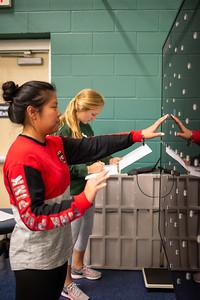 Student Cassidy Zajicek (left) takes note on Lara Bernardo's dynavision performance time for their fitness test Kinesiology lab.