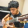 Jesse De Los Santos plays the guitar in the center for arts building.