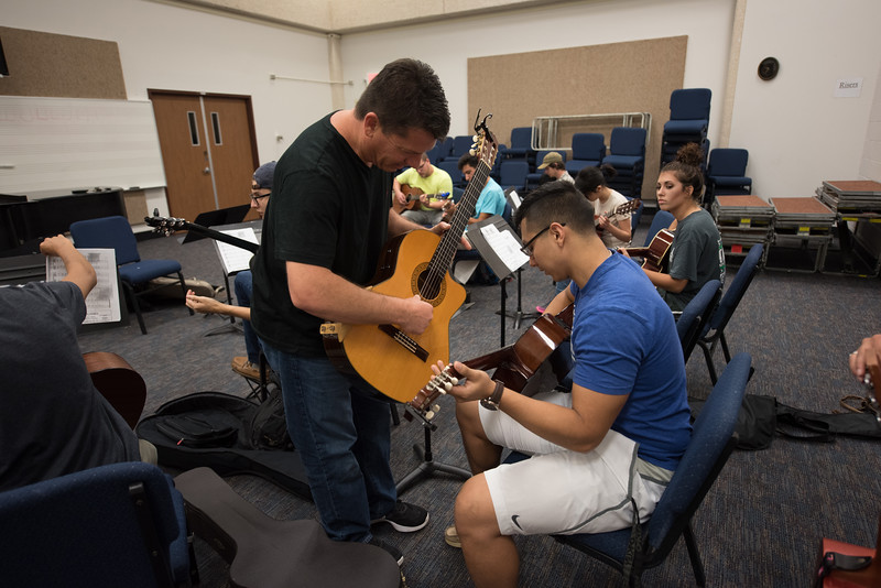 Professor Michael Moore assists students during his Basic Guitar 1 class.