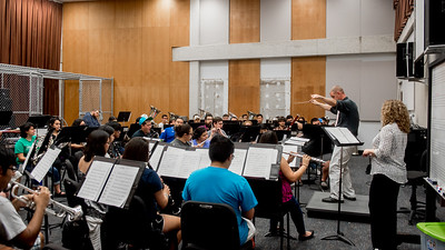 Dr. Brian Shelton as an orchestra conductor practices students to play as a symphonic wind in his Symphonic Winds class.