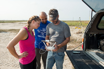 Melanie Gingrass (left), Yeoshua Cohen and Jake Berryhill with TAMU-CC's Conrad Blucher Institute; initialize a drone during their survey of Mustang Island following Hurricane Harvey's impact on the coastal bend.