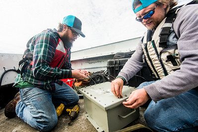 TAMU-CC Conrad Blucher Institute research engineers Hugo Mahlke (left), and Alistair Lord  prepare a module that will be attached to the buoy, during their installation of the CCPORTS system off of the Port Aransas, Tx coast.