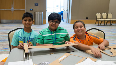 Ronit Verma, Ashrith Reddy, and Ahmed Sheta work together to build a model airplane during the UAS Camp.