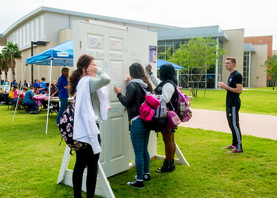 Students write words of encouragement at the Islander Cultural Alliance booth during the National Coming Out Day event on the East Lawn.