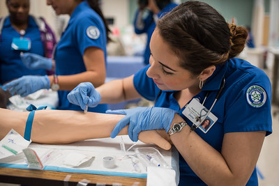 Jessica Rubles practices placing an IV on a maniquin arm.