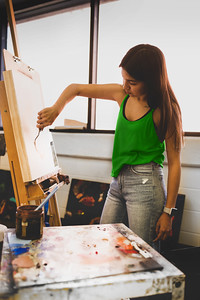 Kimberly Gary begins her Impasto Potrait for her Intermidate Painitng class by applying the first layer of paint.