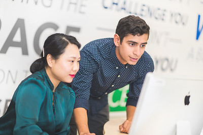 Xiuju Yao (left) and Sonny Martinez review graphic design mock up branding at the Coastal Bend Business Innovation Center.