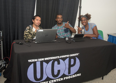Texas A&M Corpus Christi University Center Programs workers Hugo Martinez (left), Tyren Duncan, and Autumn Redmon showcase music from different countries in celebration of International Education Week.