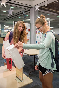 Charlotte Fleming (left), and Morgan McCutchen reveal one of the many banned books on display during the Mary and Jeff Bell Library's Banned Book Week event.