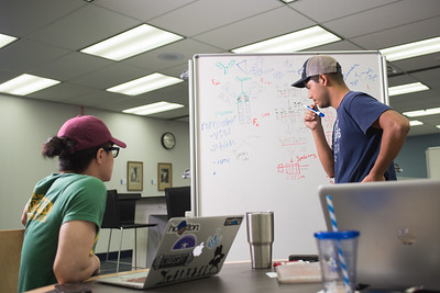 Jeno Bautista and Erik S. Soto utilizing the white boards in the Mary and Jeff Bell Library for their Immunology studies.
