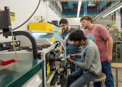 Mohammad Ahmed Hasan (front), Jose Coleman, and Tyler Woody work with metal and machinary during their Manufacturing Processes lab.