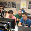 Lauren Gonzales(left) Stan Dinh, professor Jeff Spriko and Louay Bachnak go over a project in physics 1.