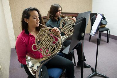 Virginia Hernandez and Jordan Gonalez play the french horn during their music education class.