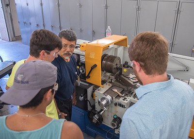 """Lab Coordinator Jack Esparza teaches students (left to right) Jerry Shea, Luke Condron, and Dante Leal how to operate a Lathe."