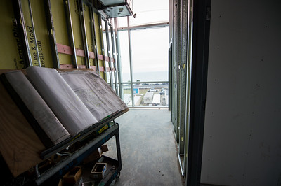 Crews work on installing wall panels on the third floor of the Tidal Hall building.