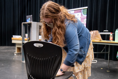 Teacher assistant Kat Williams sanitizes seating areas in preparation for her next theater class at Mary Carroll High School.