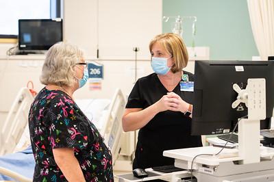 Barbara Flato (left) and Lisa Snell prepare for a virtual simulation lab.
