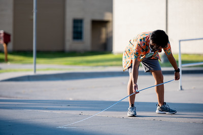 William Whitworth measures out markers for students to follow social distance guidelines during the first day on campus.