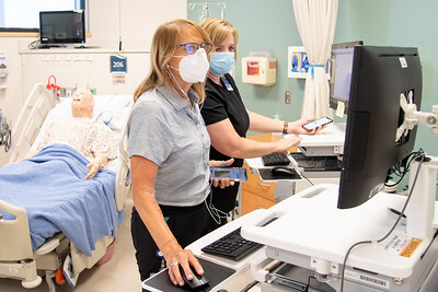 Julie Fomenko (left) and Lisa Snell prepare for a virtual simulation lab in Island Hall.