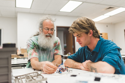 Professor Louis Katz assists student Jack Wood on the Arduino hardware used to develop interactive sculptures.