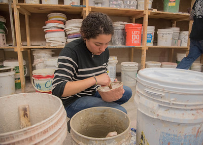 Student Ivette Perez works to glaze her ceramics project.