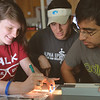 Students Sheena Hoagland(left), Fernando Torres and Brody Hajebian work together on tracing the light rays in Physic II.