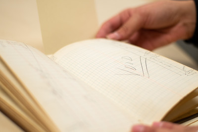 Libary Specialist Shelby Gonzalez looks through a journal archived in the Mary and Jeff Bell Library collection.
